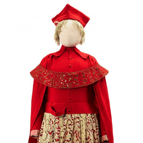 An elaborate outfit comprising a crimson robe with matching skirt with gold lace overlay. There is a sloping sash placed around the shoulders and a hat with four points.