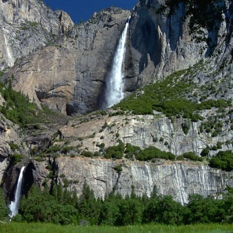 Color photo of waterfalls cascading down rocky mountains with greenery around.