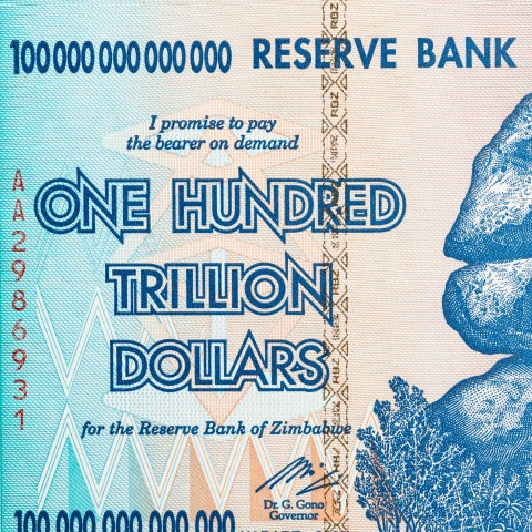 "Detail of: ""One Hundred Trillion Dollars"" bank note from ""Reserve Bank of Zimbabwe."" It is blue, turquoise, and tan in color. The central image appears to be a mountain or rock outcropping made of three large stones. Palm trees and other vegetation appears tiny at its base. Geometric patterns are included in the bill, mostly triangles."