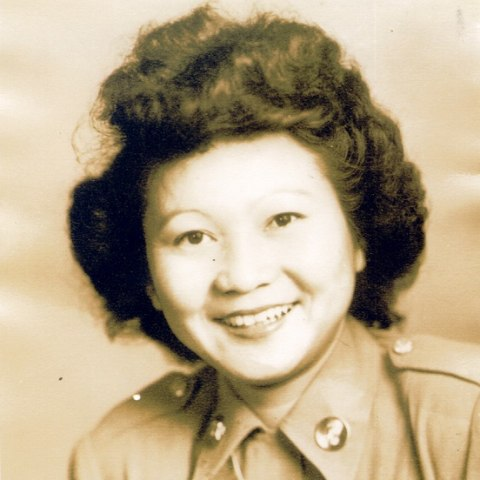 A sepia photograph of a woman with dark coiffed hair in a military-style shirt. She is smiling.
