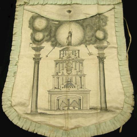 Photo of fabric apron with textured fabric around edges and scene in center with elaborate architectural design