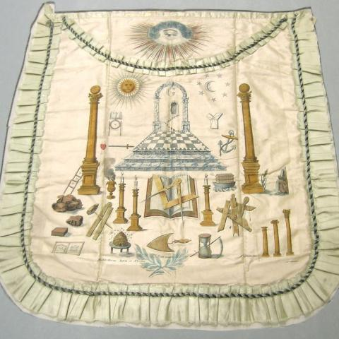 Color photo of apron with symbols on it, including hour glass and columns