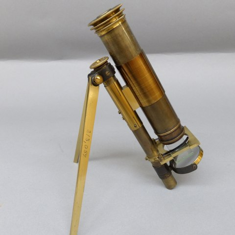 Microscope, bronze in color, on small tripod. Small glass in viewer.