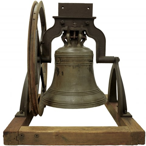A picture of a large bell on wooden supports. There is a metal wheel next to it on its large frame