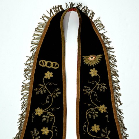 An image of a violet fraternal collar--opulently decorated with golden embroidery and a hand painted eye