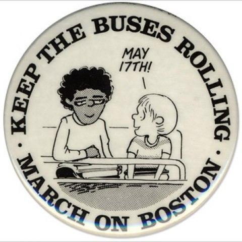 """White button features a drawing of two students sitting next to each, one turns to the other and says """"May 17th!."""" Around the button's border the text reads: """"Keep the Buses Rolling...March on Boston."""""""