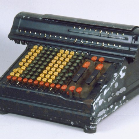 black metal device that looks like a typewriter. All the keys, however, have numbers on them and they are yellow, green, and red.
