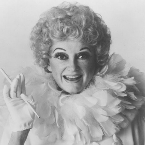 A woman in a short blond curly wig with a white top with a large feather neckling. She holds a cigarette holder in her hand.