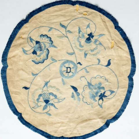 A white doily with blue embroidery.