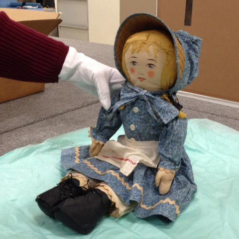 """Curator preparing """"Abigail"""" doll for display in the """"American Enterprise"""" exhibition."""