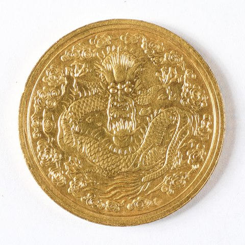 A gold coin. It is very bright and has a long, snakelike dragon coiled in the middle with cloud-like designs around it.