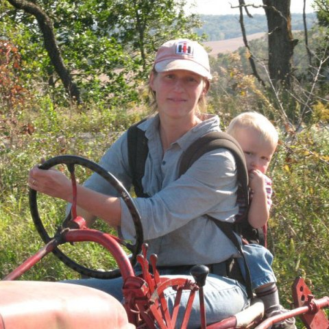 A woman in a photograph drives a red farm machine on a hill in the countryside. She looks at the camera, wearing a baseball cap and denim shirt. Strapped to her back is a baby who looks at the camera suspiciously.