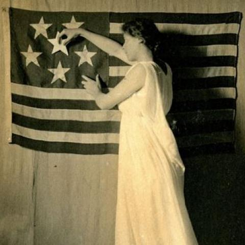 In this 1911 postcard created by the National American Woman Suffrage Association, the stars on the flag represent states that have voted for suffrage.