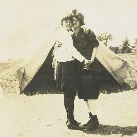 Two campers embrace in front of a tent