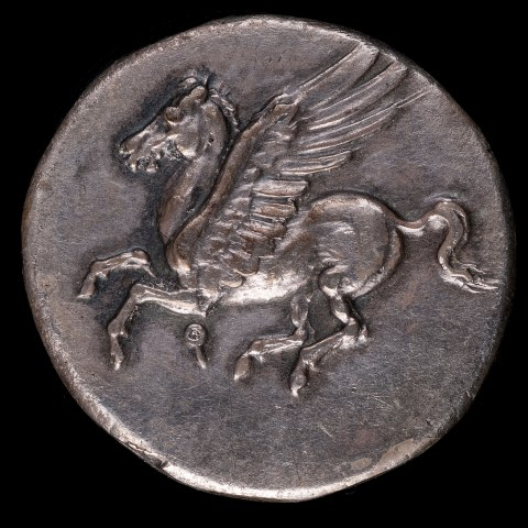 A silver coin with a pegasus in flight on it
