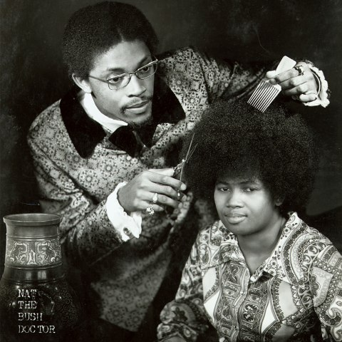 A black and white photograph of a man in a patterned jacket and wire-rimmed glasses hovering over a boy with an Afro. The man holds a pair of scissors and a wide-toothed comb over the boy's hair as he looks off.