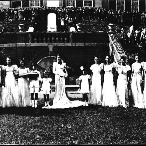 Thirteen women and three children pose in floor-length dresses outside a building with fountain