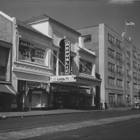Black-and-white photo of buildings on a street, including Republic theater with marquee. American flag over an office building. Two people walk down sidewalk.