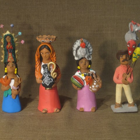Four figurines lined up against a background. They wear colorful clothing, carry different items and have objects on their heads