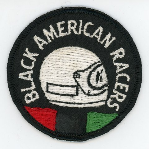 A black patch with a white helmet sewn on the front