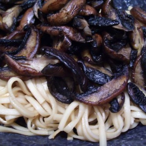 Mushrooms, sauteed in butter, sit on top of pasta