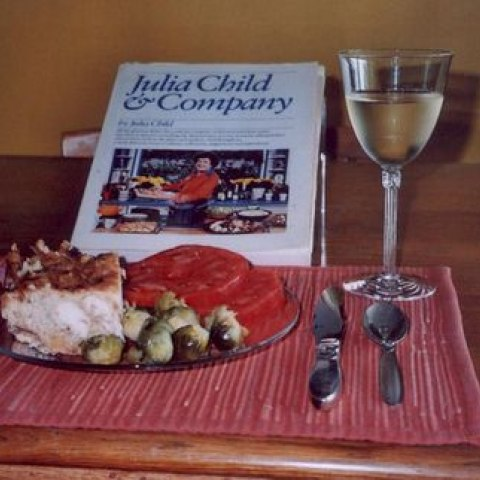 Turkey Orloff, made using a recipe created by Julia Child, sits on a plate at a dinner table place setting, next to a Julia Child & Company cookbook