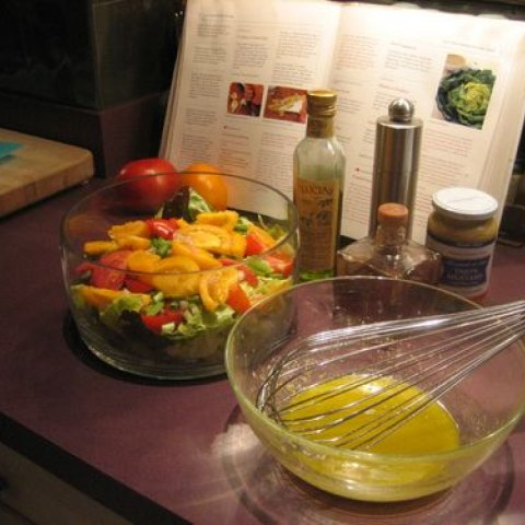 A bowl of vinagrette, created with a recipe made by Julia Child, sits next to a bowl of salad and a Julia Child cookbook