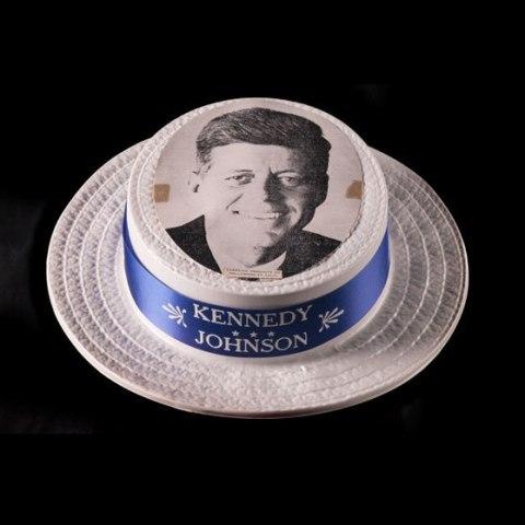 White hat with blue ribbon and black and white photo of John F. Kennedy smiling