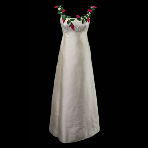 A white debutante gown with an empire waste and fabric flowers around the neckline.