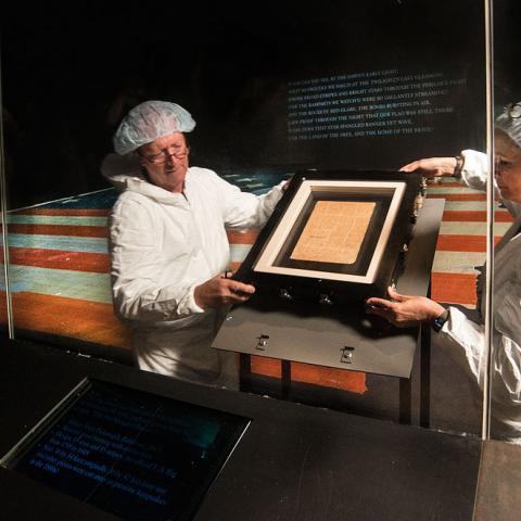 Staff members in Star-Spangled Banner gallery installing manuscript