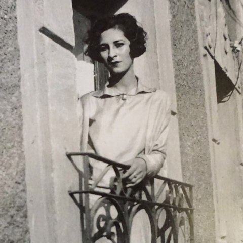 A woman with styled hair leans out a window.