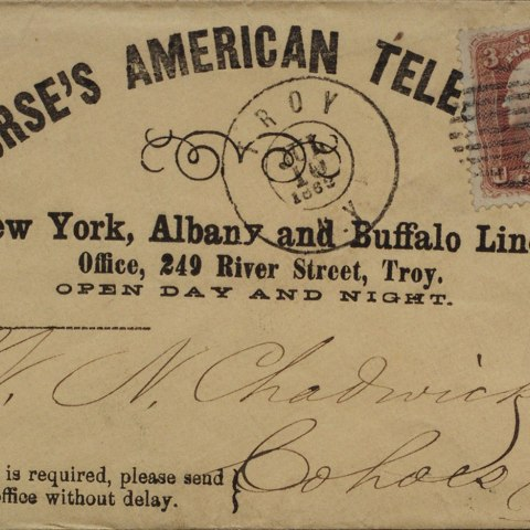 """an envelope that reads """"Morse's American Tele"""" from an office in Troy, NY. The paper is faded and has cursive writing on it."""