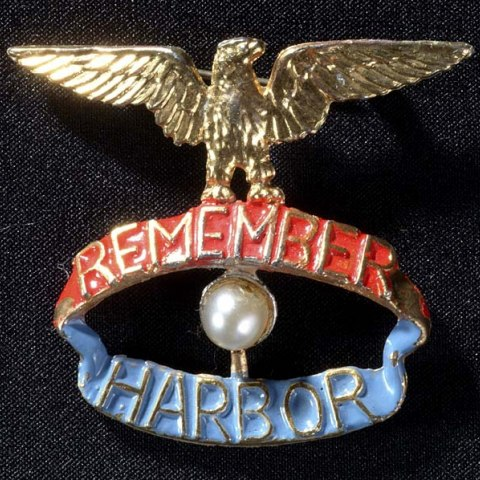 "A pin, presumably for a woman. There is a gold eagle perched on top with its wings outstretched. It stands on top of a red banner saying ""Remember"" which is over a blue banner that says ""Harbor"" Between the banners is a pearl."