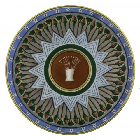 A saucer with geometric patterns and shades of blue, green, and red. There is a prominent lotus decoration.