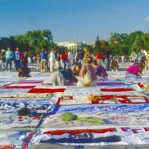 Quilt spread out with many people looking at it, some kneeling