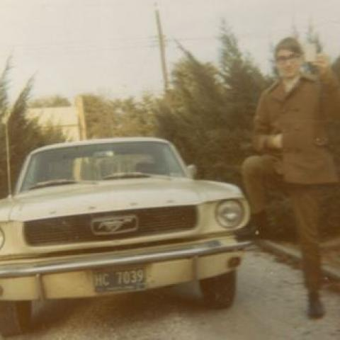 On the left, a 1966 Ford Mustang (yellow). On the right, a young man holding keys. Photo is from 1970s.