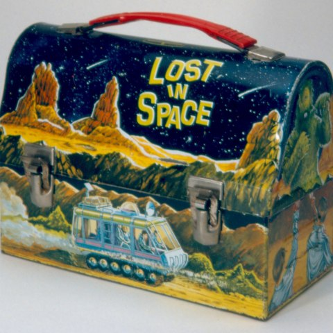 A lunchbox with a rectangular base and a curved top. It has a red handle and metal clasps. Its surface depicts a barren landscape with a starry night sky. A futuristic silver van on many wheels drives across the front. On the side, one can see two people with their arms raised. A giant green monster stands in front of them.
