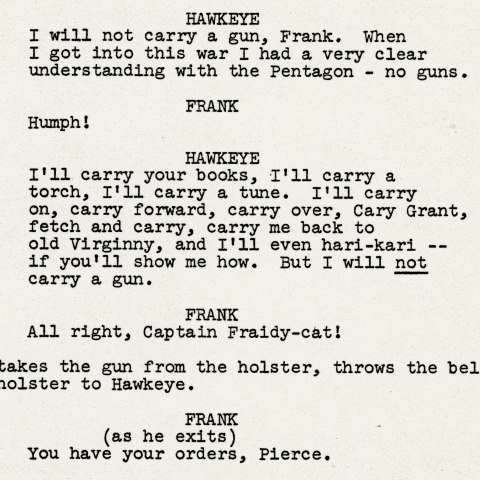 A page from a television script. The paper is beige colored and the text looks like it is from a typewriter and is centered on the page