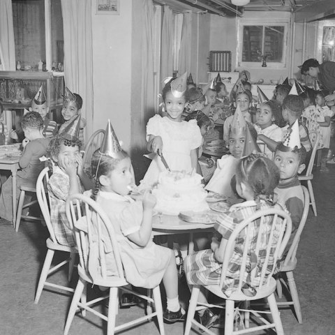 A young girl stands behind a cake in a room full of seated children wearing party hats.