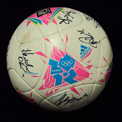 a white soccer ball with pink and blue designs advertising the london 2012 olympics and signatures in black sharpie