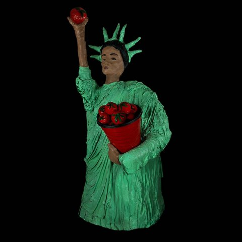 A statue or object resembling the statue of Liberty. The robe and crown are a mint green color and The statue holds an apple up. There are more in a container she holds at her side. She has dark hair and olive brown skin.