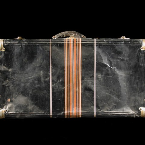 A black suitcase whose case is old and warped with stripes down the center under the handle.