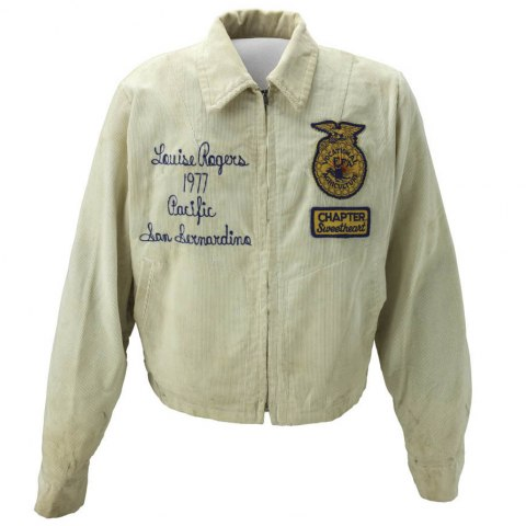 Against a blank white background, a white corduroy jacket with with an insignia on the left breast and stitching on the right