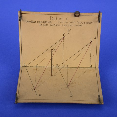 """A piece of tan-colored paper folded in half. One half is lying flat and the other is open facing the camera, like an open mouth. There are geometric drawings on the paper with strings attached. The top says """"Relief e"""" with text below it in French."""