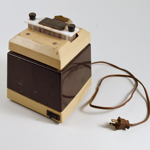 A cubed machine that is beige and brown in color. It has a switch near its base and a plug. Some features protrude from it, including a white piece on the top that has slats in it.