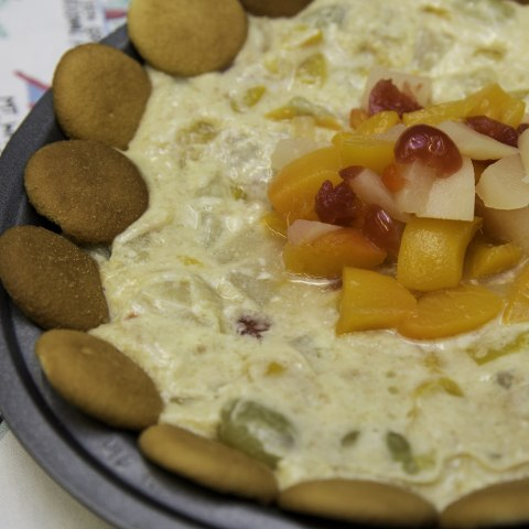 A pie in a dish that is crustless and looks like cream with pieces of fruit mixed in. In the middle are a number of pieces of fruit (the type that come in a fruit cocktail) piled up and the pie is lined by a ring of Nilla wafers.