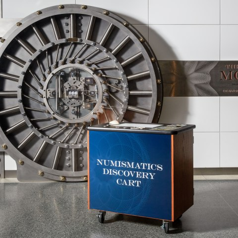 A small, cabinet-like square cart with 4 wheels, a blue front, and items on top sits in front of a giant vault door set against the wall with a sign for the value of money exhibit.