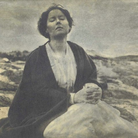 A photograph that is awash in tones of gray. A woman sits in a moor-like environment with a white dress and black shawl or robe. Her face is lifted up and her eyes are closed. Her hands are clasped together as if in prayer