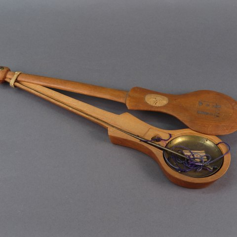 A wooden case with the cover pushed to the side. Inside there is a metal dish attached to a stick with purple strings.