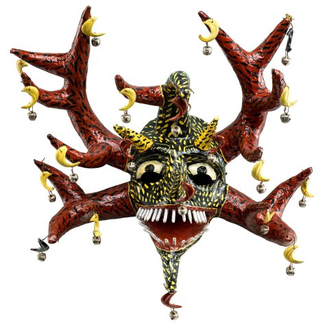 A colorful mask with red antlers, a black face covered in yellow dashes with two yellow horns. The eyes are exaggeratedly large and the mouth is open with many thin white teeth. There are bells attached all over the mask.